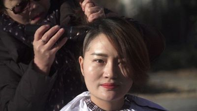 Wife of detained China lawyer goes bald for justice