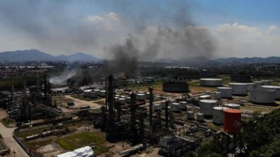 Firemen work to put out fire at Rio oil refinery