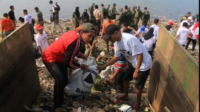 Hundreds sift through rubbish wasteland on Indonesia beach