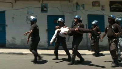 Comoros police carry unconscious man during Moroni protests