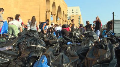 Day after protests, Lebanese don gloves and clean up