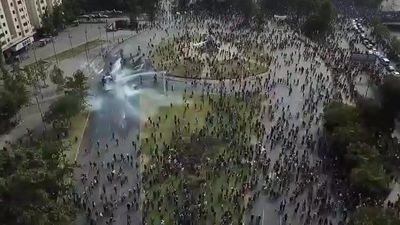 Aerial shots of water cannons spraying crowd of protesters in Santiago
