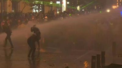 Lebanese forces use water cannons during clashes outside Parliament