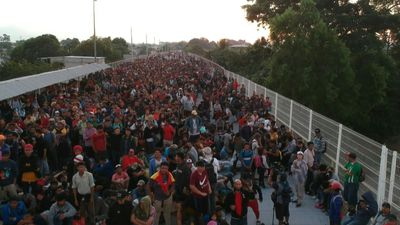 Thousands of migrants await to enter Mexico legally on border bridge