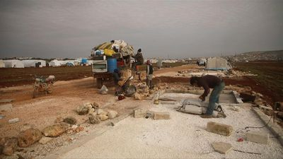 Syrians flee a displaced camp in the north of Idlib province