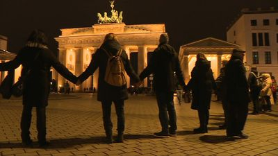 Berliners form human chain at the Brandenburg Gate after Hanau shooting