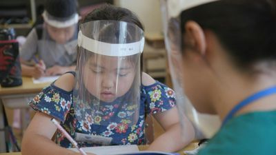 Japanese students go back to school, with face shields