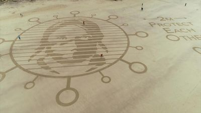 English sand artists create giant beach drawing to promote social distancing