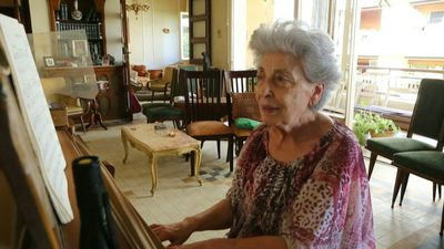 Elderly woman finds solace in music amidst destruction