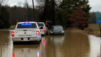 Video shows woman climb out of car in flood