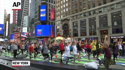 Hundreds take to Times Square for solstice yoga