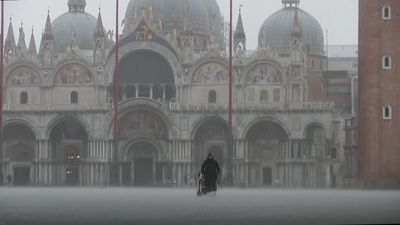 Tourists, Venetians slosh through flooded city