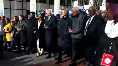 Democratic contenders link arms in MLK Day march