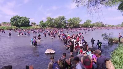 Migrants wade across river, trying to enter Mexico