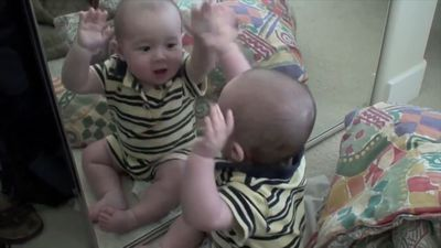 Baby thrilled by his own reflection in mirror