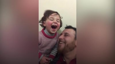 Syrian father teaches daughter to laugh at sound of air strikes