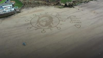 Sand artists highlight need for social distancing