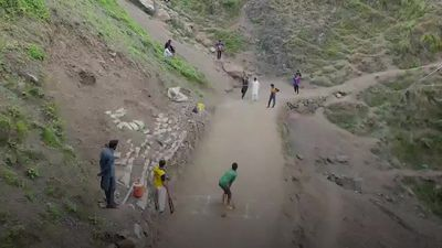 Cricketers in Pakistan play on improvised hilly pitch