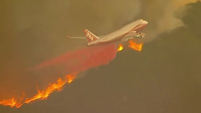 Jet drops fire retardant liquid on raging Orange County blaze