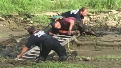 Man and pet parrot rescued from waist-deep mud