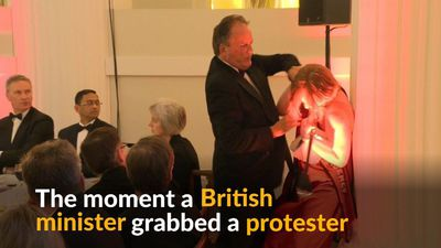 British minister suspended after grabbing protester by neck