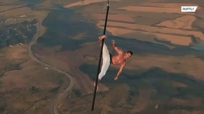 Russian daredevil performs bone-chilling stunts while suspended from hot air balloon