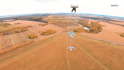 Gymnasts perform stunning feats while gliding 600 metres above Siberian tree tops