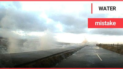 This is the scary moment a dad and son were nearly swept away by storm waves which engulfed their ca