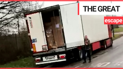 A group of men are seen running away after jumping out the back of a lorry