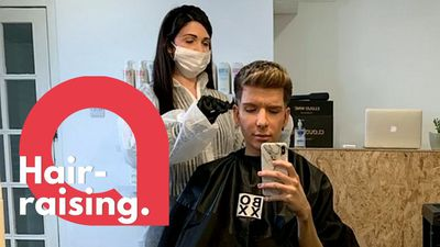 Student gets hair cut by hairdresser in a 'Coronavirus suit'