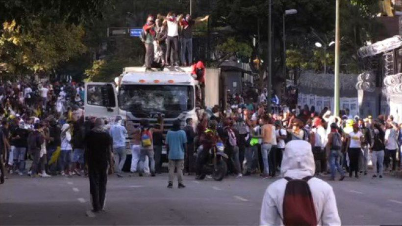 Protesters in Venezuela commandeer a truck as hundreds cheer