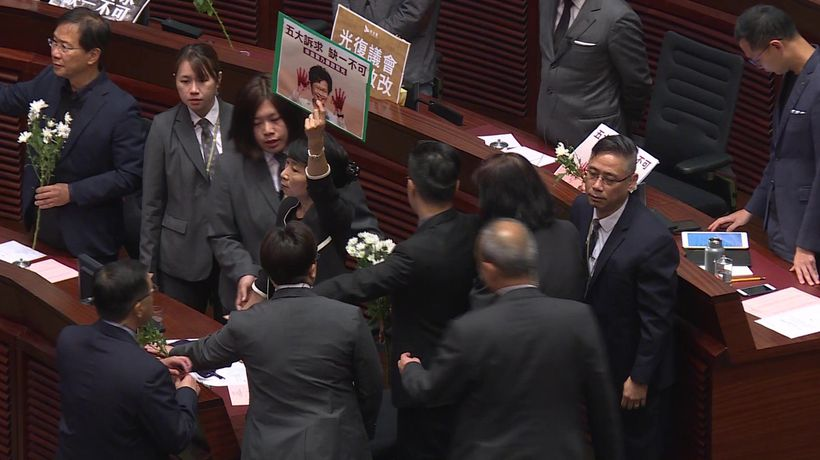 Hong Kong lawmakers dragged from chamber as leader heckled for second day