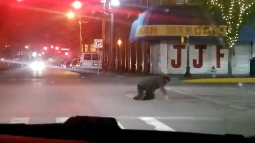 Driver films people crawling out of manhole cover