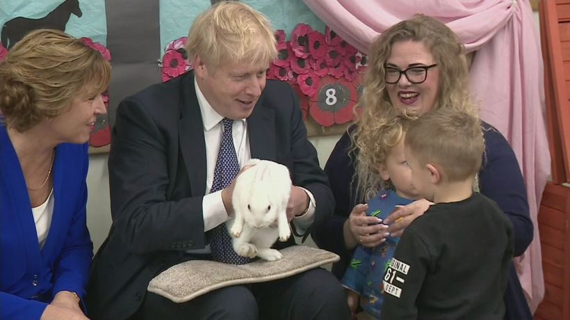 PM cuddles Rosie the rabbit and sings songs with pupils