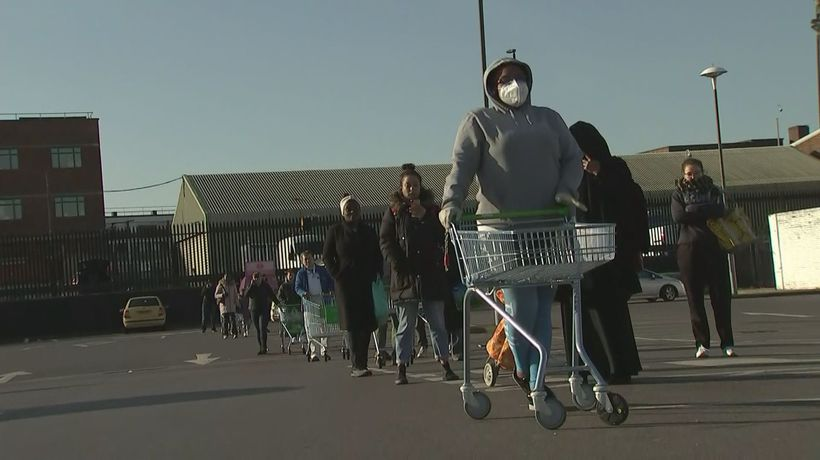 Shoppers queue outside supermarkets amid lockdown