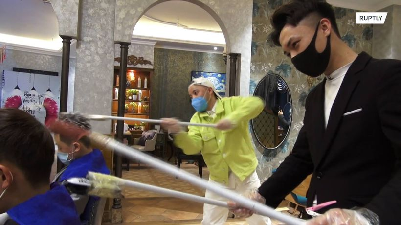 Chinese hairdressers uses poles to keep distance with customers amid coronavirus