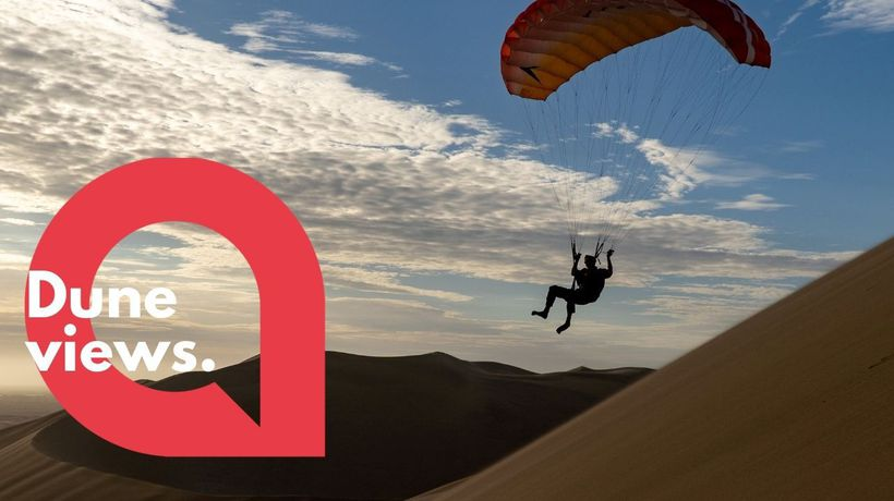 This mesmerising footage shows a daring paraglider floating over picturesque rolling sand dunes