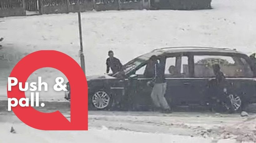 Strangers rushed out in freezing conditions to help a hearse up a hill after it got stuck in the sno