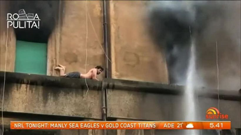 Man escapes apartment inferno by clinging to side of building