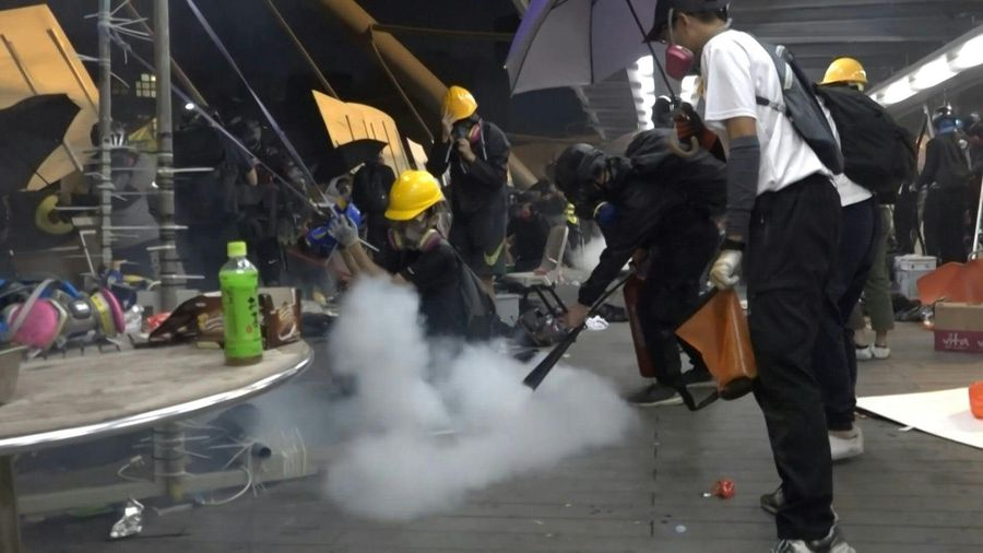 Hong Kong protesters fight back police tear gas