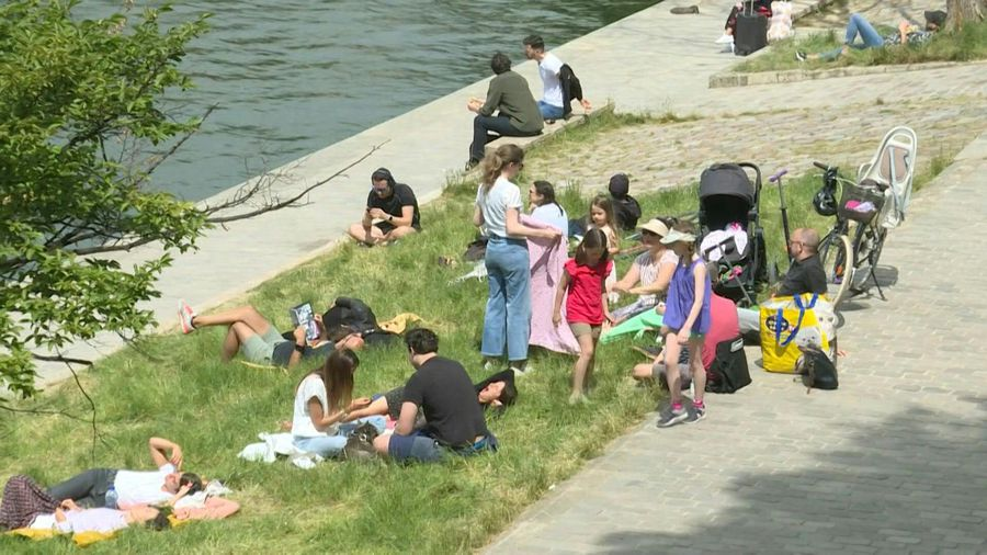 Parisians enjoy a stroll on the banks of the Seine River