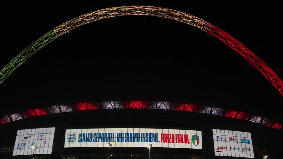 Wembley stadium lights up in Italian colours in homage to game that was supposed to be played