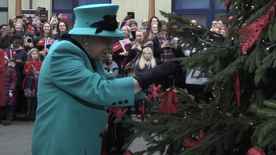 Queen helps girl hang decoration on Christmas tree
